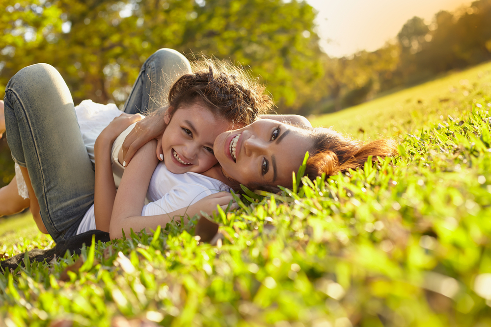 Mother and child playing on grass, hugging and smiling