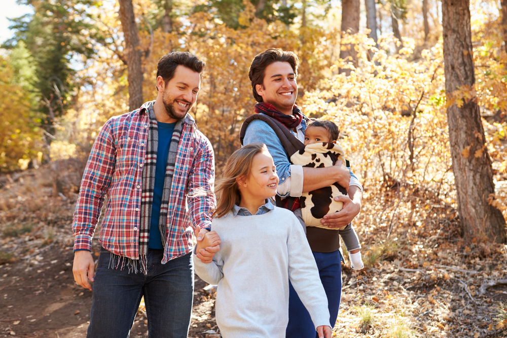 Gay male couple with two adopted children, walking happily in woods