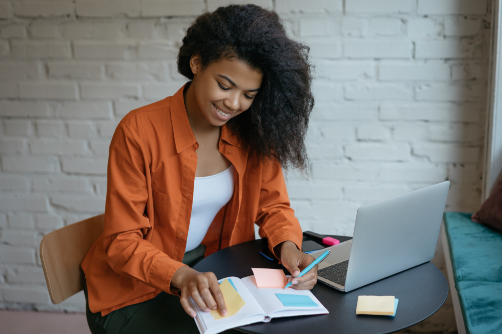 Woman working at laptop, smiling and being productive