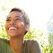 A young African-American woman smiling outdoors.