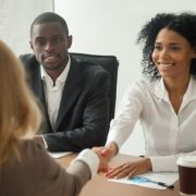Work colleagues in meeting, two women shaking hands with man sitting at table