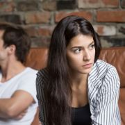 Upset couple after fight, sitting on couch looking away from each other