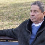 Pensive older man sitting on park bench looking away