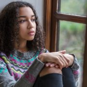 Sad teen girl with curly black hair looking out window