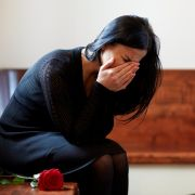 Woman in black dress, crying in church pew with rose; she is grieving a death
