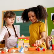 Three children playing with wooden blocks in classroom