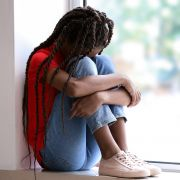 Sad girl with braids sitting on windowsill with head on her knees