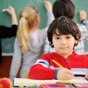 Boy in red hoodie holding pencil in classroom, looking at camera