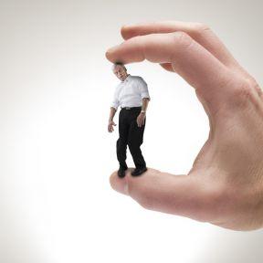 Big hand crushing tiny powerless businessman