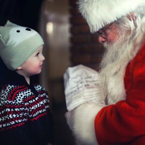 Young child receiving a gift from Santa Claus.