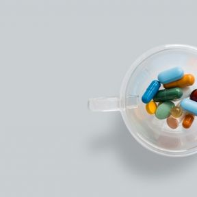 transparent coffee cup with colourful pills on gray background.