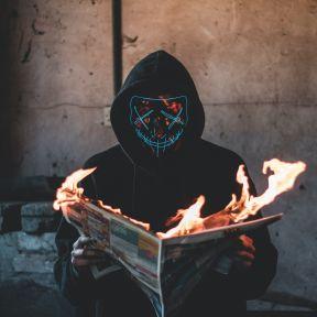 一个蒙面的,连帽的形象拿起燃烧的报纸