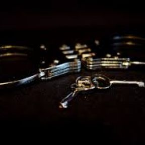 Image: Silver handcuffs with keys on black background