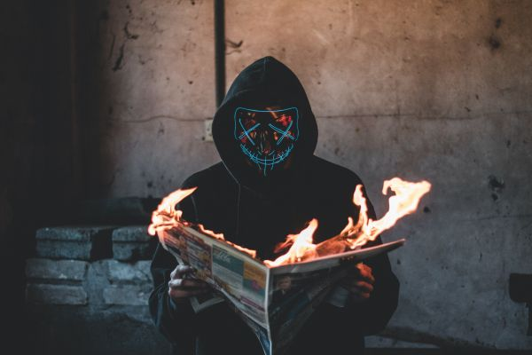A masked, hooded figure holds up a burning newspaper