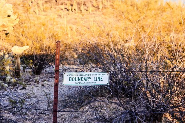 Fence with boundary line sign.