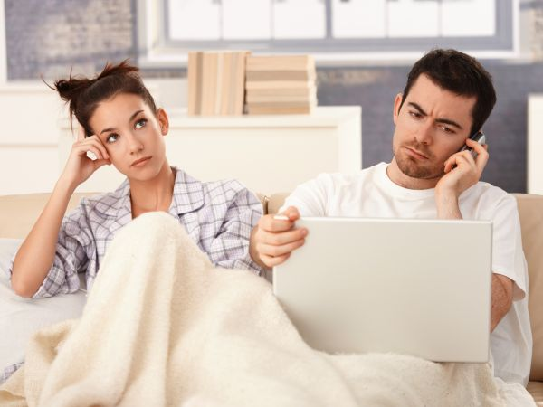 Man uses technology in bed while wife is bored