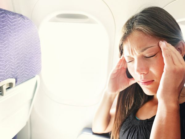 Stressed out woman on plane touches head