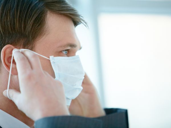 Professional man fearful of airborne illness puts on face mask