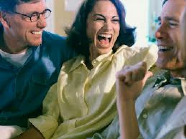 A woman smiling and laughing with two men