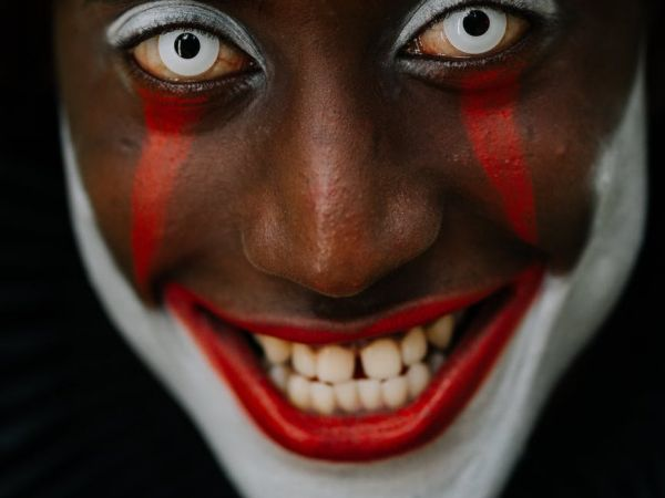 A clown with bright white contacts and red and white makeup smiles a sinister smile