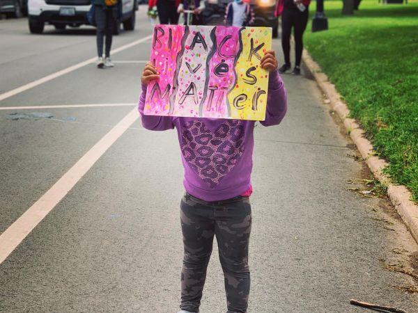 A child holding up a Black Lives Matter sign
