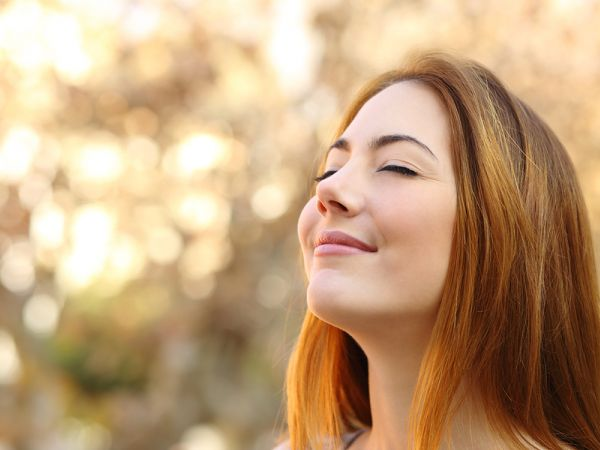Confident woman smiles peacefully with her eyes closed