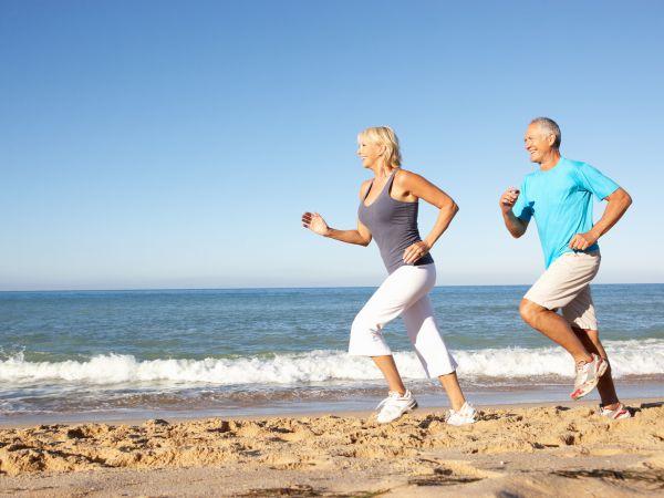 A middle-age couple run along the beach