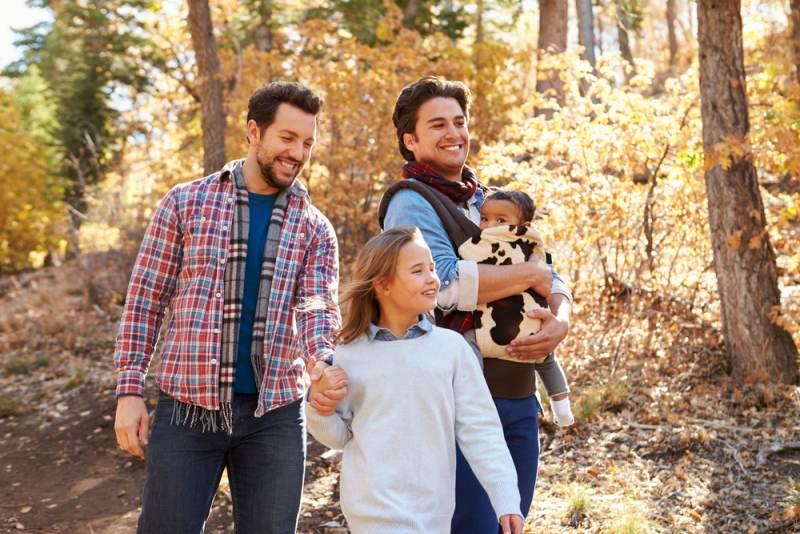 Una pareja de dos hombres gay con dos niños adoptados caminando felices en el bosque.