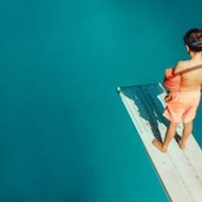 Top view of boy standing on spring board learning to dive.
